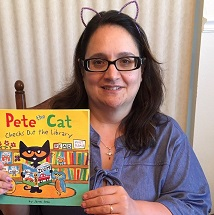 "CHildren's Librarin Miss Marie holidng up ""Pete the Cat"" book"