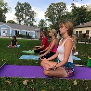 Teens doing yoga on the lawn