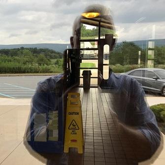 Reflection of man taking photo through window