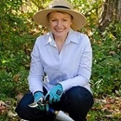 Michele MacKinnon kneeling in garden with gardening shovel