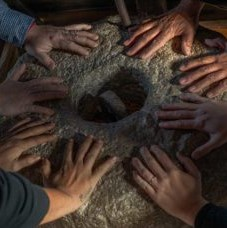 six sets of hands in a circle on the ground
