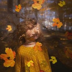 autumn leaves falling on little girl