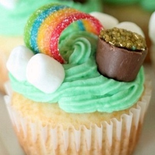 vanilla cupcake with green icing, mini marshmallows and rainbow fruit roll-up