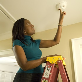 woman standing on ladder checking fire detector