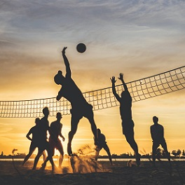teens playing volleyball on beach