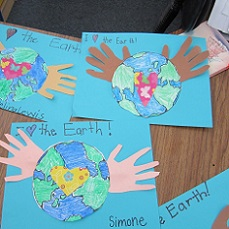 child's drawing of he earth with paper hands attached