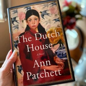 a hand holding a copy of the book The Dutch House