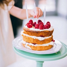 strawberry shortcake on a cake plate with child placing candles in it