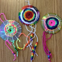 colorful yarn and beads wrapped around recycled CDs