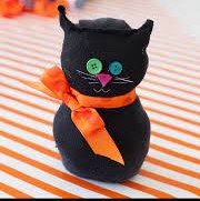 black cat made from a sock with buttons for eyes and orange scarf