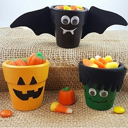 planter pots decorated to look like a pumpkin, bat with wings and Frankenstein
