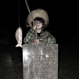 boy dressed as a ghostly boy from the past with a fishing pole, leaning on a headstone in cemetary