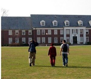 three students with backpacks walking across the lawn heading towards college building