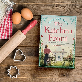 """book titled """"The Kitchen Front"""" on a cutting board with a rolling pin, eggs and cookie cutters"""